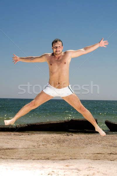 Dziwaczny młody człowiek skoki plaży człowiek ciało Zdjęcia stock © acidgrey