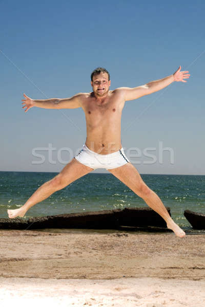 Bizar jonge man springen strand man lichaam Stockfoto © acidgrey
