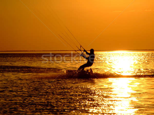 Silhouette of a kitesurf on a gulf on a sunset 2 Stock photo © acidgrey