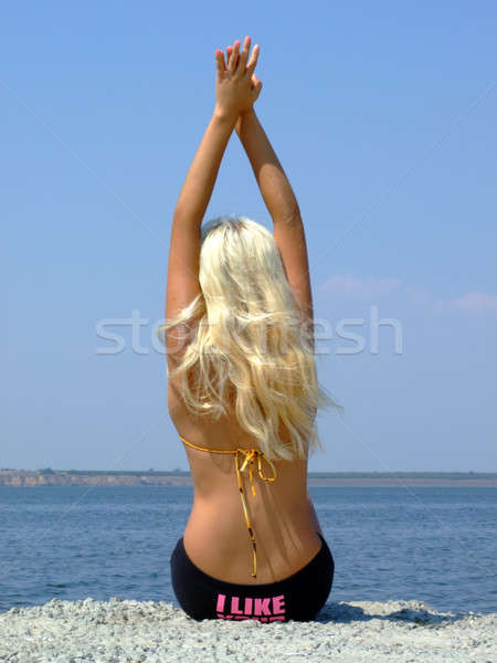 Stock photo: The girl-blonde sits on coast of a gulf, having lifted hands upw