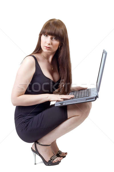 Stock photo: The young businesswoman sits with the laptop in a lap