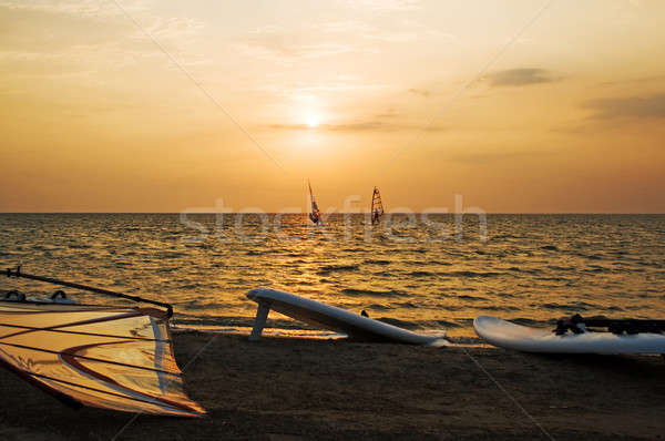 Silhouette of a two windsurfer on a gulf on a sunset Stock photo © acidgrey