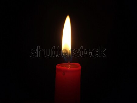 Stock photo: The red candle burning in full darkness