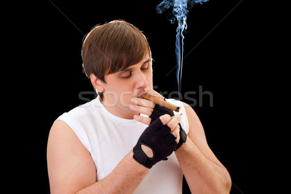 Young man sets fire to a cigar Stock photo © acidgrey