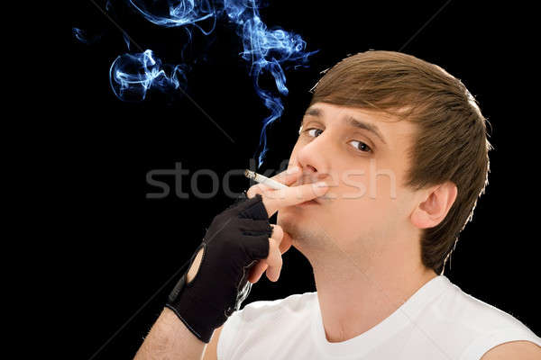 Young man smoking a cigarette. Isolated on black Stock photo © acidgrey