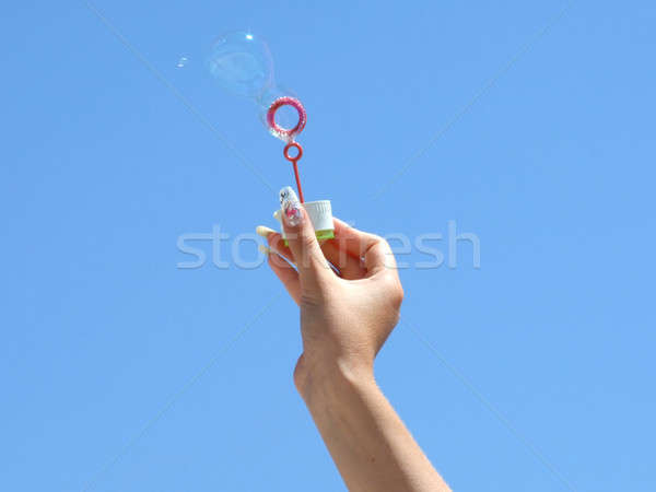 Female hand and soap bubbles on a background of the blue sky Stock photo © acidgrey