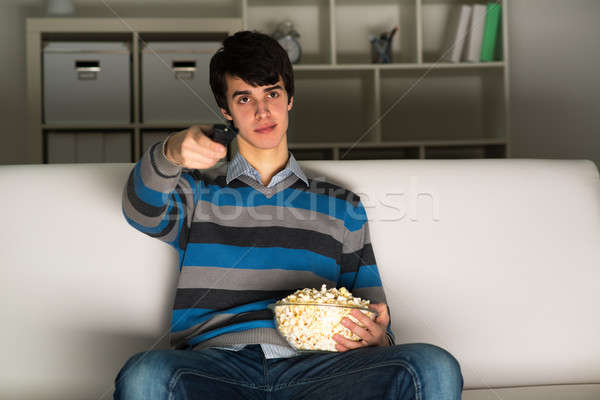 young man watching television with popcorn Stock photo © adam121