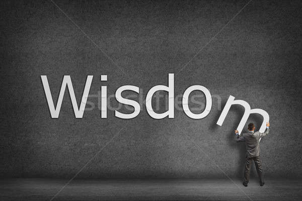 Businessman collects on the wall the word wisdom Stock photo © adam121
