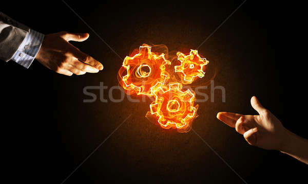 Concept of teamworking or organization presented by hands in touch and fire glowing cogwheels Stock photo © adam121
