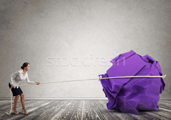 Woman pulling with effort big crumpled ball of paper as creativity sign Stock photo © adam121