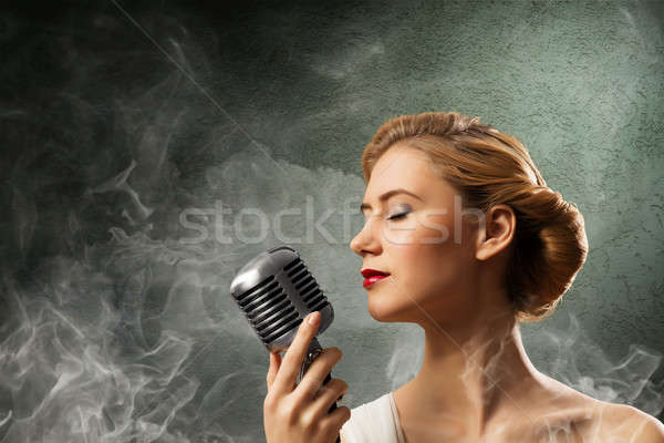 Stock photo: beautiful blonde woman singer with a microphone