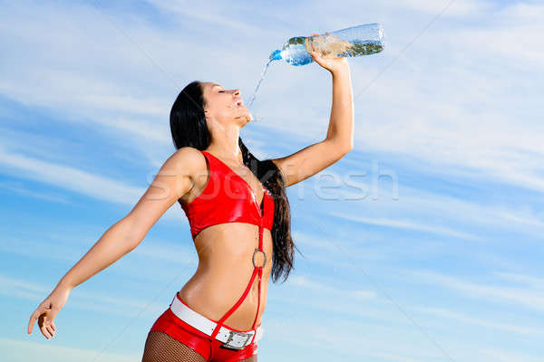 woman in a red dress drinks water from a bottle Stock photo © adam121