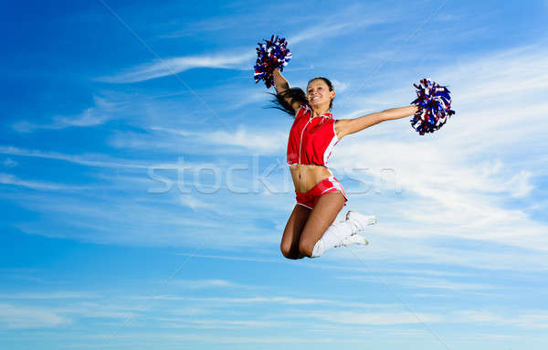 Stock photo: Young cheerleader in red costume jumping