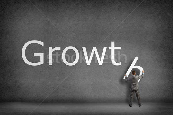 Businessman collects on the wall the word growth Stock photo © adam121