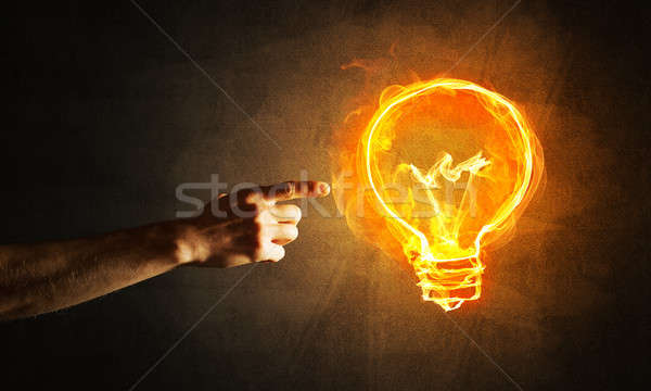Concept of electricity or inspiration with burning light bulb and creation gesture Stock photo © adam121