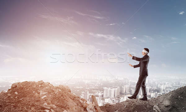 Young businessman in blindfold walking carefully and cityscape at background Stock photo © adam121
