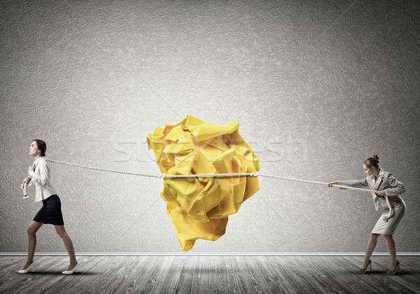 Two women pulling with effort big crumpled ball of paper as creativity sign Stock photo © adam121
