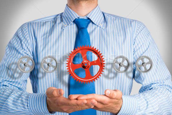 business man holds up a mechanism of gears Stock photo © adam121