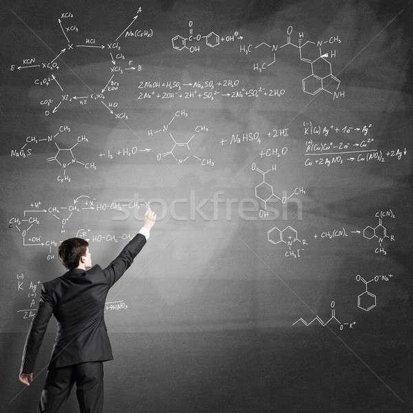 Cientista escrita fórmulas quadro-negro moço terno Foto stock © adam121