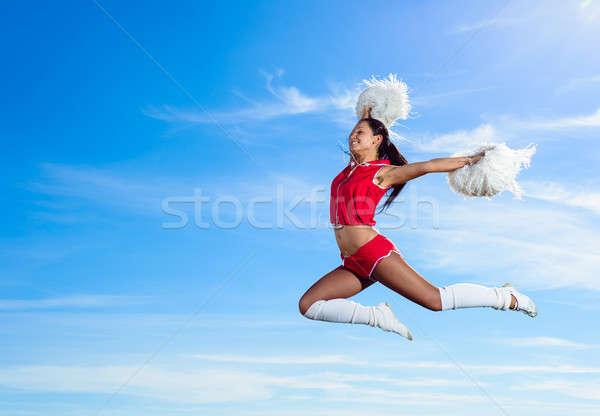 Fiatal pompomlány piros jelmez ugrik kék ég Stock fotó © adam121