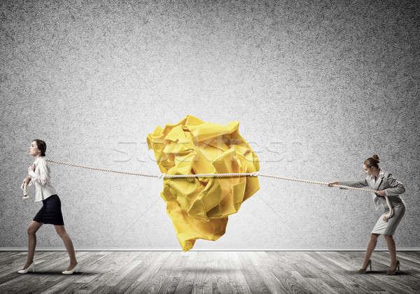 Two women pulling with effort big crumpled ball of paper as crea Stock photo © adam121