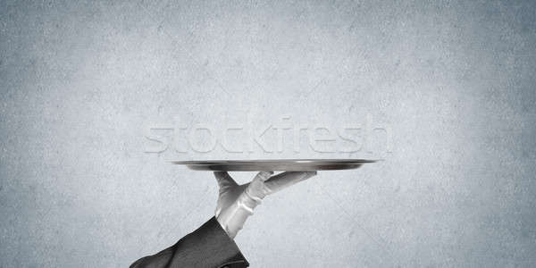 Hand of butler holding empty metal tray against concrete background Stock photo © adam121