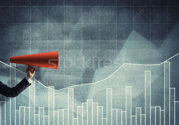 Hand of businesswoman holding red paper trumpet against graphs b Stock photo © adam121