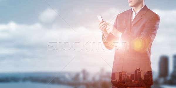 üzletember mobiltelefon kitettség modern város kéz Stock fotó © adam121