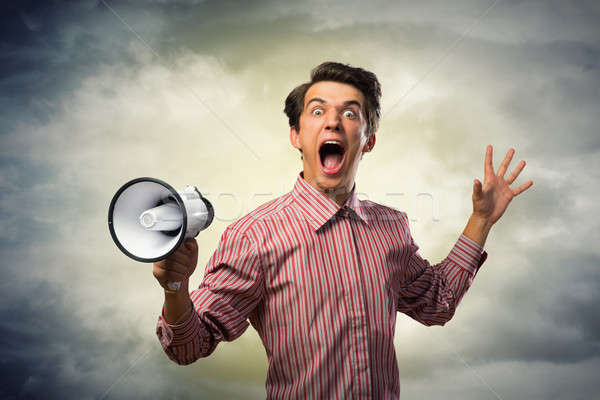 Portrait of a young man shouting using megaphone Stock photo © adam121