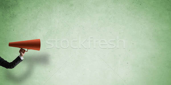 Hand of businesswoman holding red paper trumpet against concrete background Stock photo © adam121