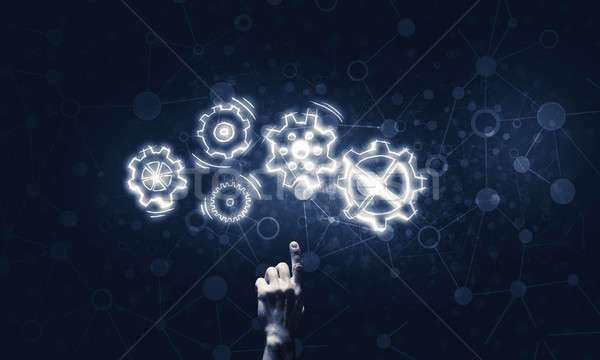 Glowing cogwheel mechanism icon on dark background as symbol of  Stock photo © adam121