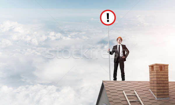 Businessman on house top showing sign with exclamation mark. Mix Stock photo © adam121