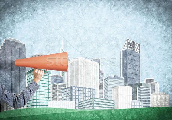 Hand of man holding orange paper trumpet against illustrated bac Stock photo © adam121