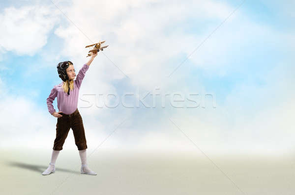 girl in helmet pilot playing with a toy airplane Stock photo © adam121