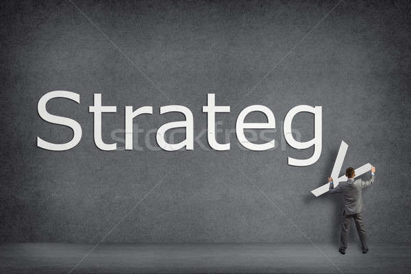 Businessman collects on the wall the word strategy Stock photo © adam121