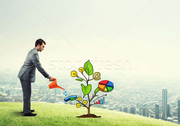 Young businessman outdoors watering drawn growth concept with can Stock photo © adam121