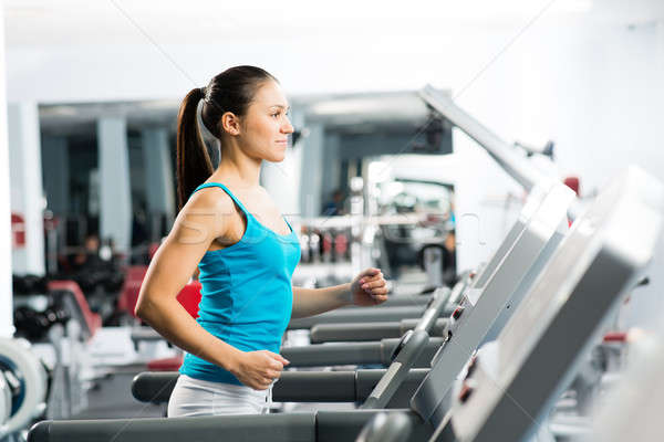 attractive young woman runs on a treadmill Stock photo © adam121