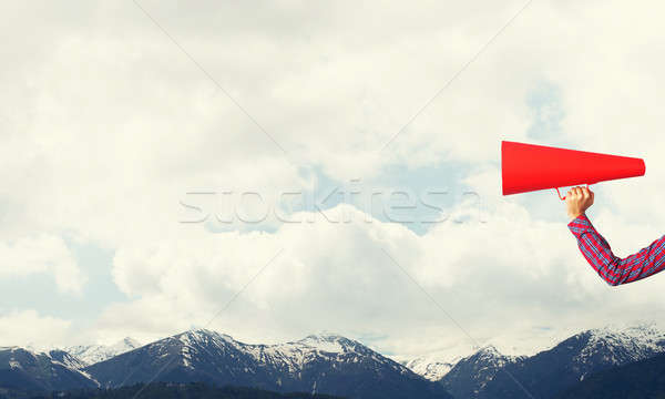 Hand of woman holding paper trumpet against natural landscape background Stock photo © adam121