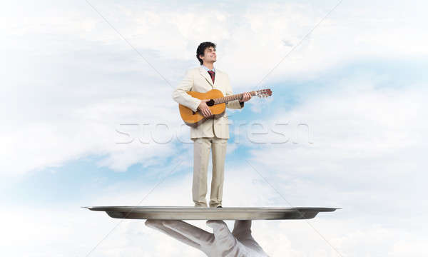 Businessman on metal tray playing acoustic guitar against blue sky background Stock photo © adam121