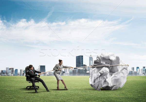 Stock photo: Businesspeople pulling with effort big crumpled ball of paper as creativity sign