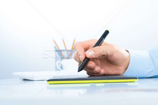 Designer hand drawing a graph on the tablet Stock photo © adam121