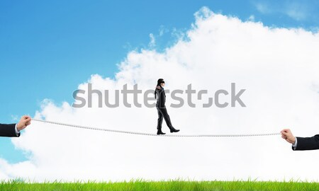 Young businessman in blindfold against white background walking on rope Stock photo © adam121