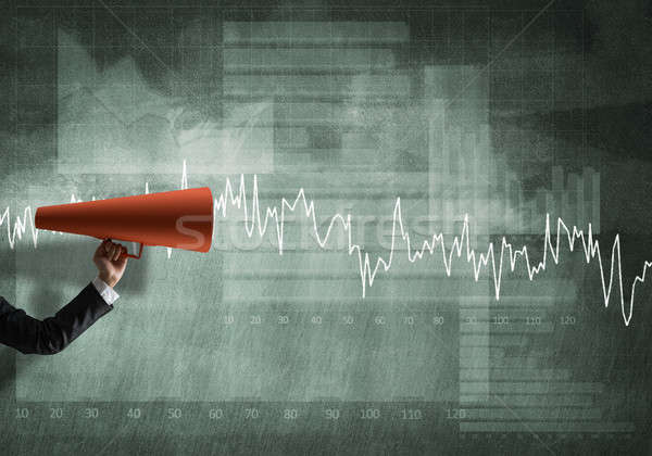 Hand of businesswoman holding red paper trumpet against graphs background Stock photo © adam121