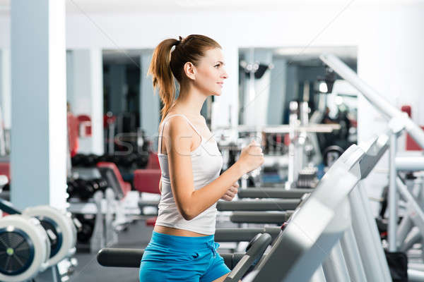 attractive young woman runs on a treadmill Stock photo © adam121
