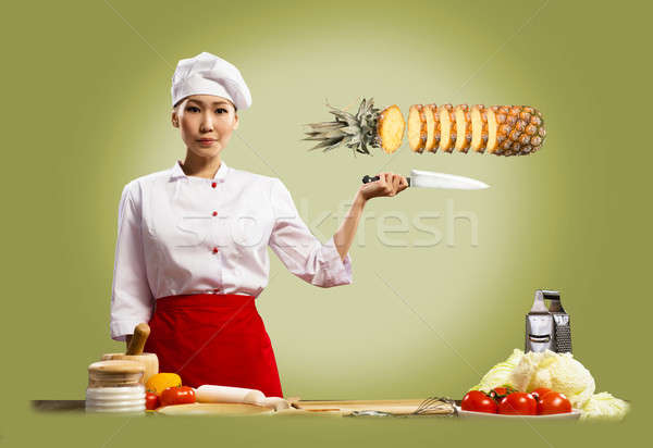 Stock photo: Asian female chef cuts pineapple