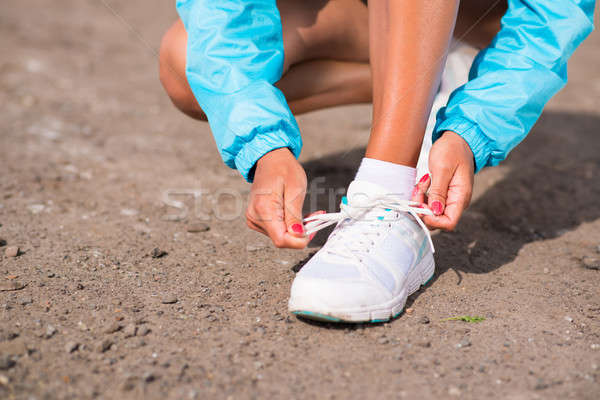 young woman tying shoelaces on sneakers Stock photo © adam121