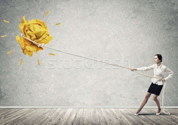 Businesswoman pulling paper ball with rope and making it raise u Stock photo © adam121