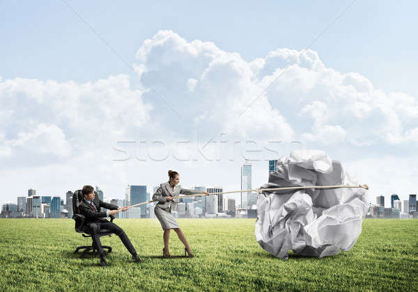 Businesspeople pulling with effort big crumpled ball of paper as Stock photo © adam121