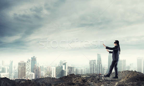 Young businessman in blindfold walking carefully and cityscape a Stock photo © adam121