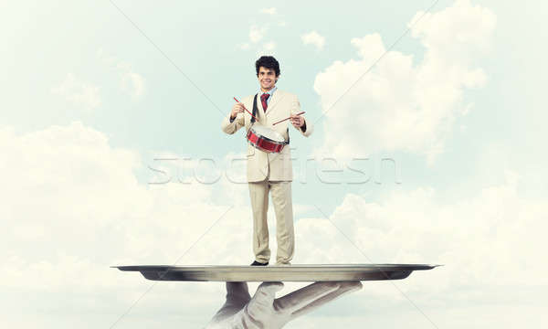 Stock photo: Young businessman on metal tray playing drums against blue sky b